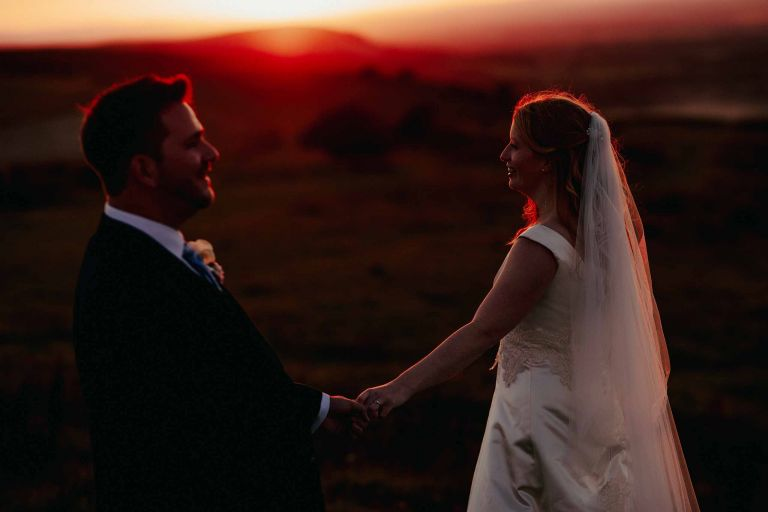 Bride and groom hold hands on the Ditchling Beacon at sunset