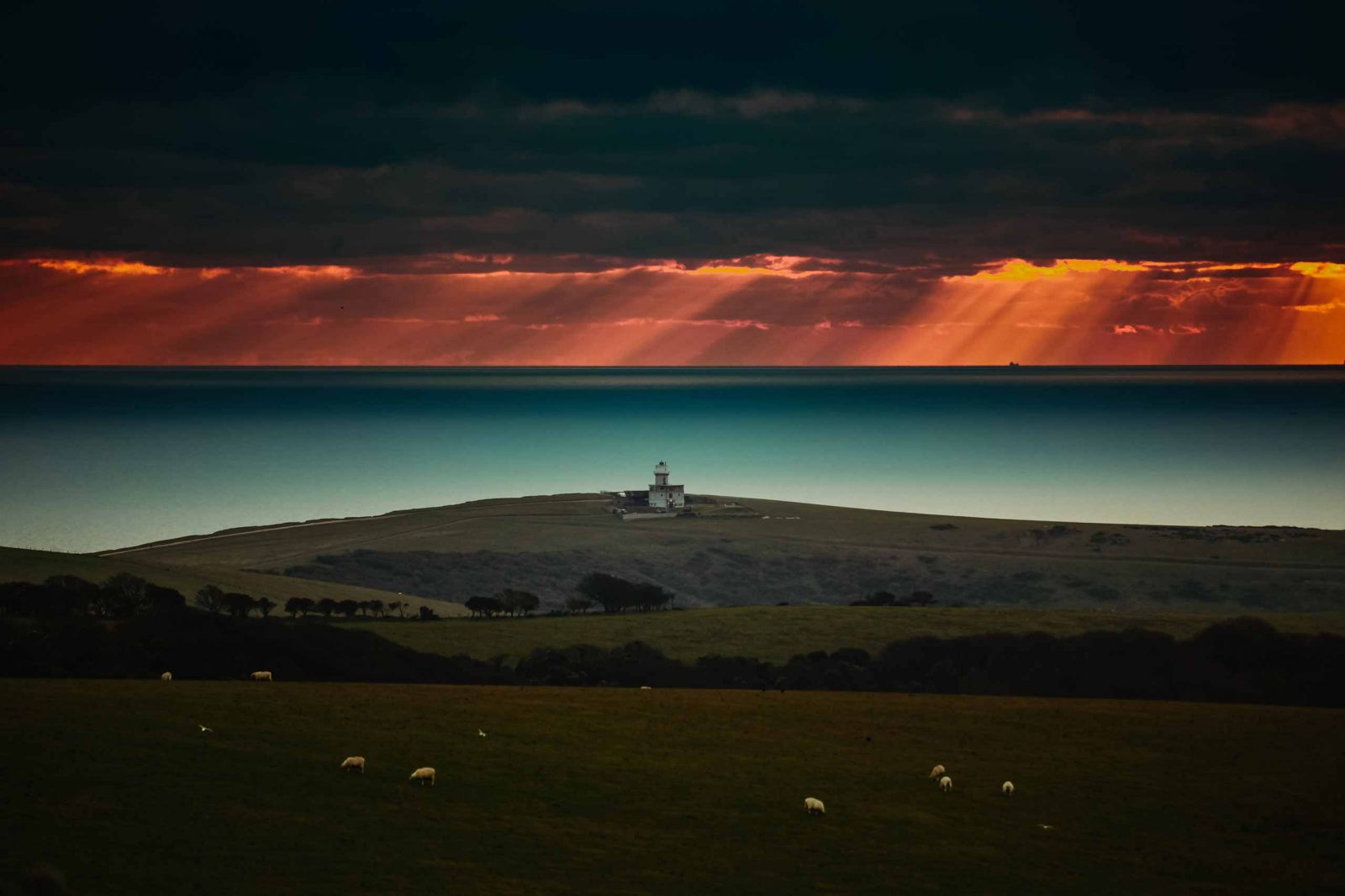 Belle Tout lighthouse shot across the South Downs towards the sea at sunset