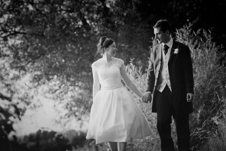 50's bride and groom walking hand in hand at their coltsford mill wedding