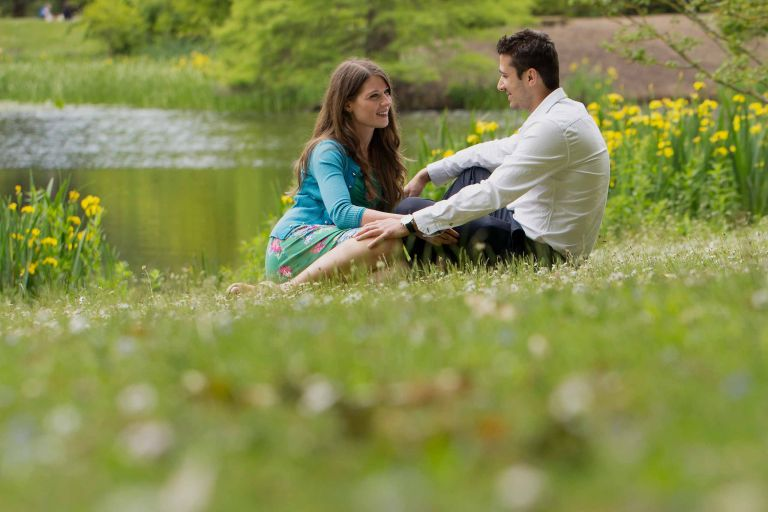 Couple sitting in the grass together during their Kew Gardens engagement shoot